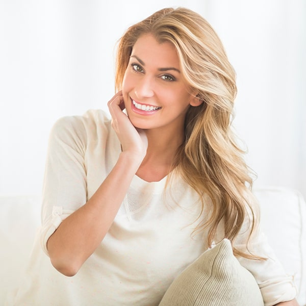 A blonde woman smiling while touching her cheek