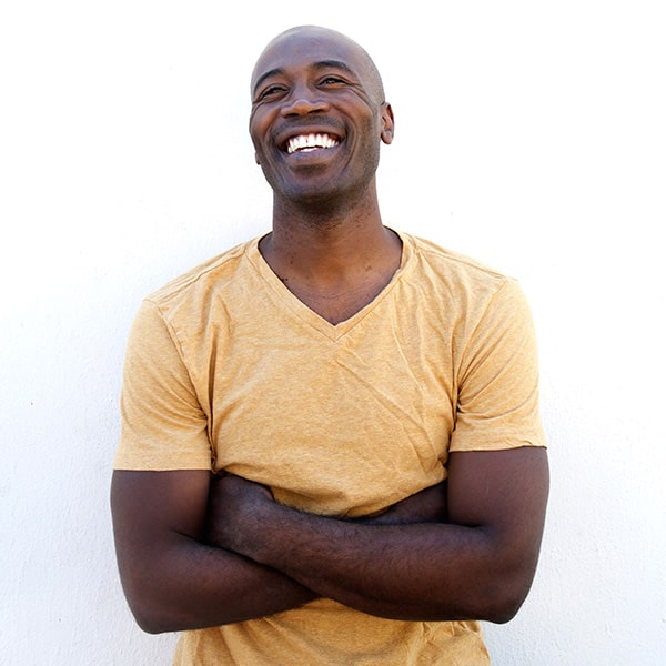 A middle-age man smiling while crossing his arms