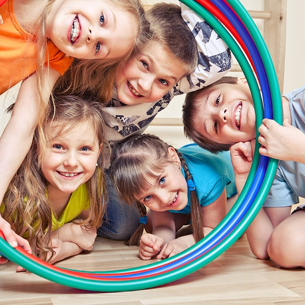 Five Children playing with hoops while smiling