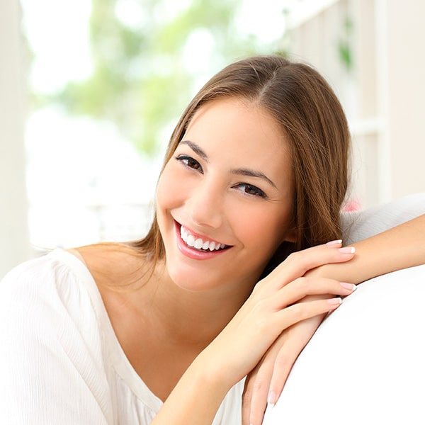 A woman smiling on a sofa