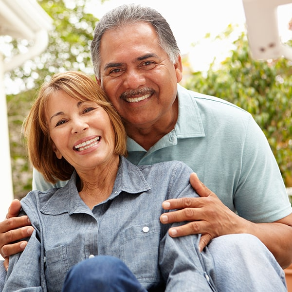 An older couple smiling as they hug in a garden