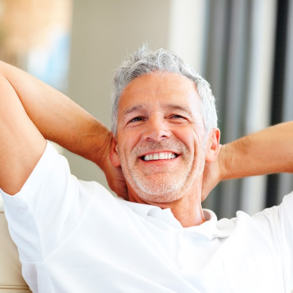 An older man sitting on the sofa while smiling