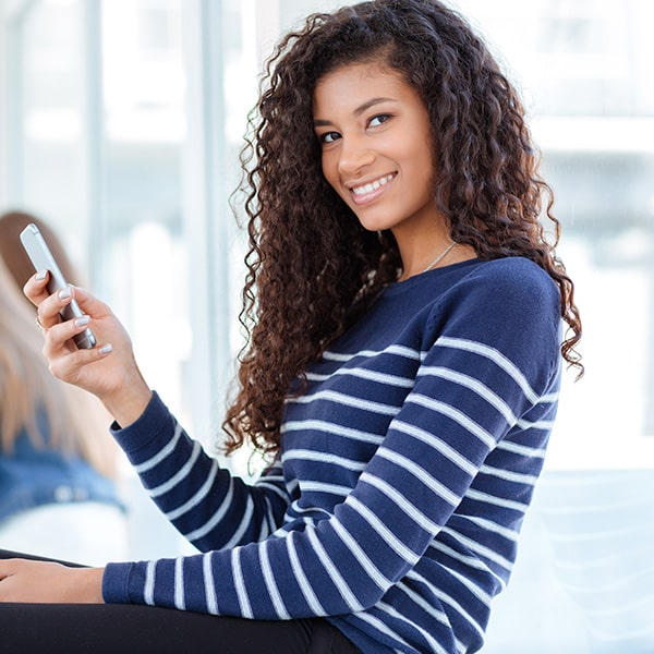 A young woman smiling while using her cell phone