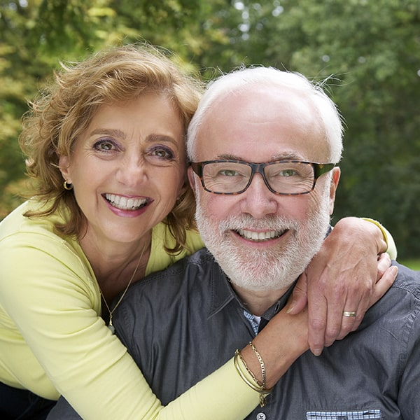 A mature couple hugging in the garden while smiling