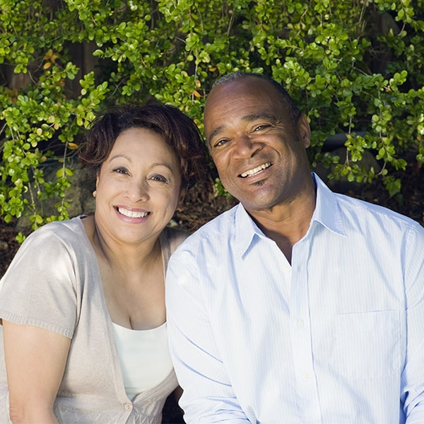 A couple in a garden smiling after their CEREC treatment