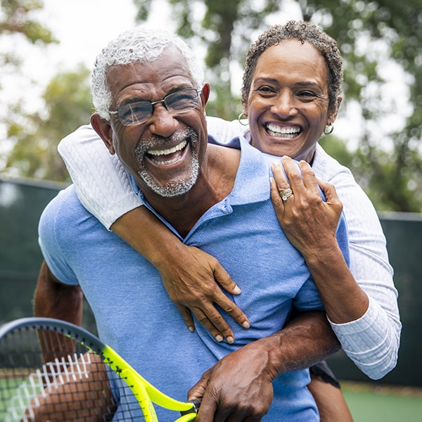 A mature couple smiling while playing tennis and hugging
